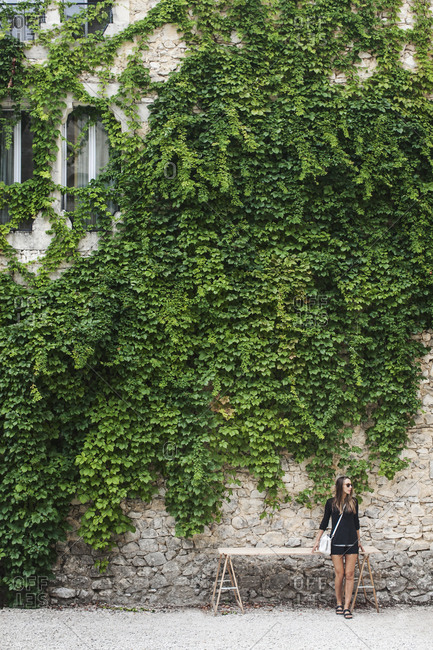 Chic woman by ivy-covered house