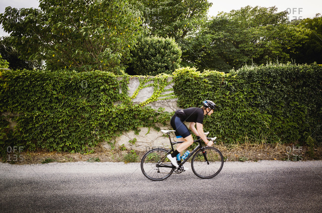 Cyclist racing past rustic house