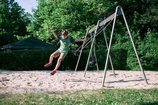 Boy jumping off a swing
