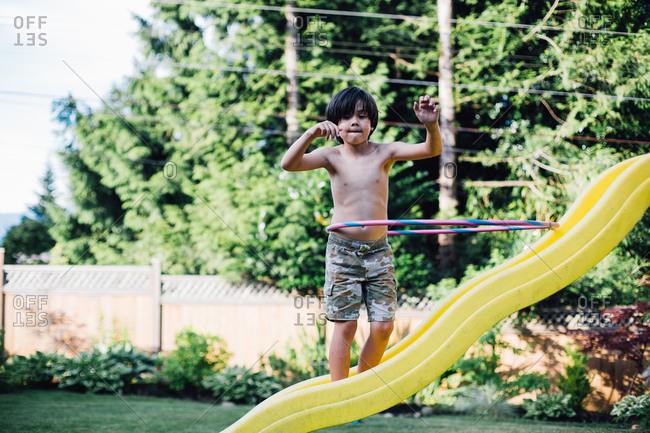 Boy hula hooping on slide