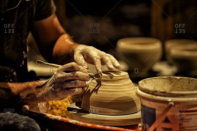 Potter shaping a pot on a wheel
