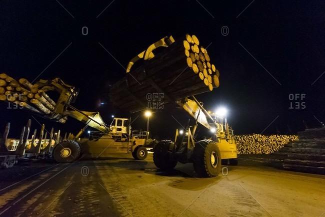 Log handling forklift trucks at night