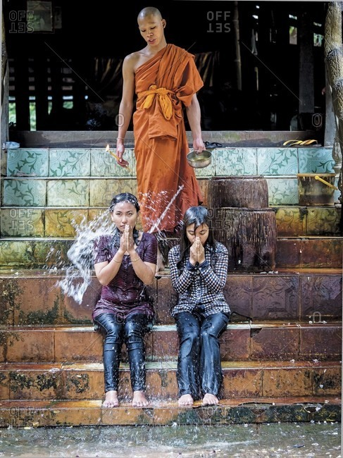 Angkor Wat, Siem Reap, Cambodia - July 8, 2013: Buddhist monk blessing two women at Angkor Wat, Siem Reap, Cambodia