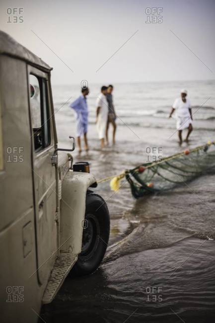 Men using truck for fishing in Oman