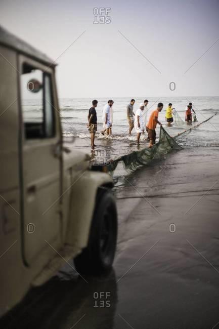 Muscat, Oman - October 18, 2011: Truck hauling in fishing net in Oman