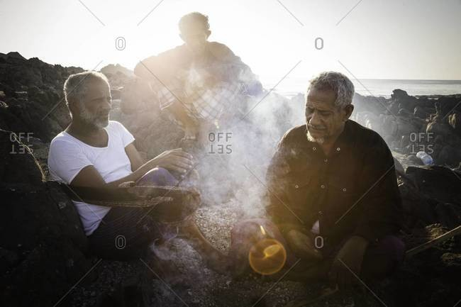 Muscat, Oman - October 20, 2011: Fisherman gathered on beach in Oman