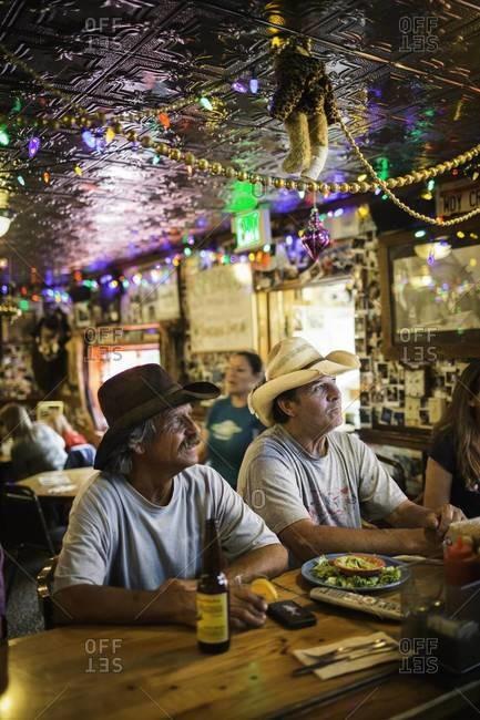 Aspen, Colorado, USA - July 1, 2012: Men watching TV in tavern, Colorado
