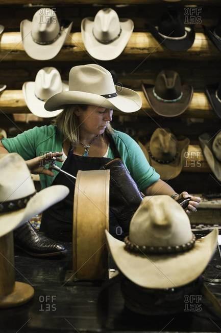 Aspen, Colorado, USA - July 3, 2012: Woman adjusting boot in cowboy shop