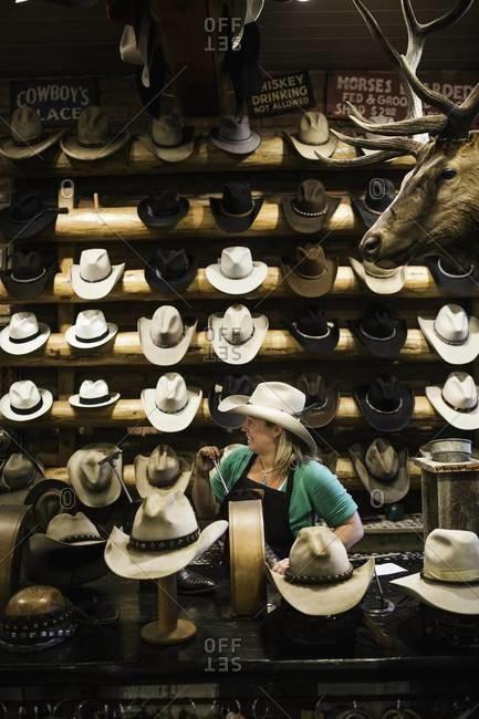 Aspen, Colorado, USA - July 3, 2012: Woman fixing boot in cowboy shop
