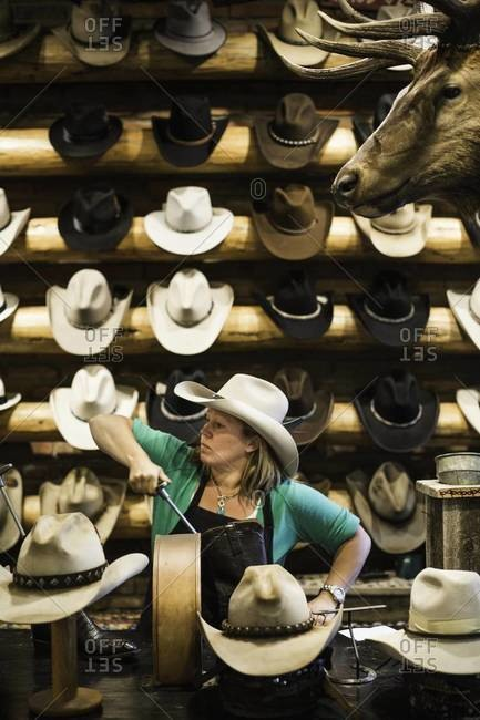 Aspen, Colorado, USA - July 3, 2012: Woman fixing boot in cowboy store