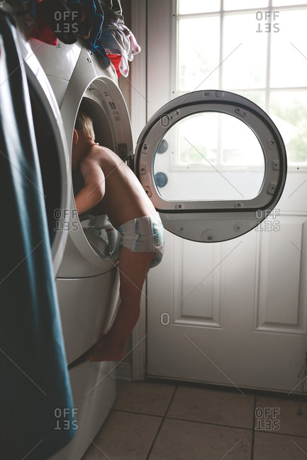 Curious boy looking into a dryer