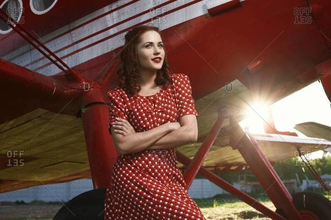Woman in retro dress with a vintage red biplane