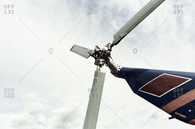 Close-up view of helicopter tail rotor against gray sky