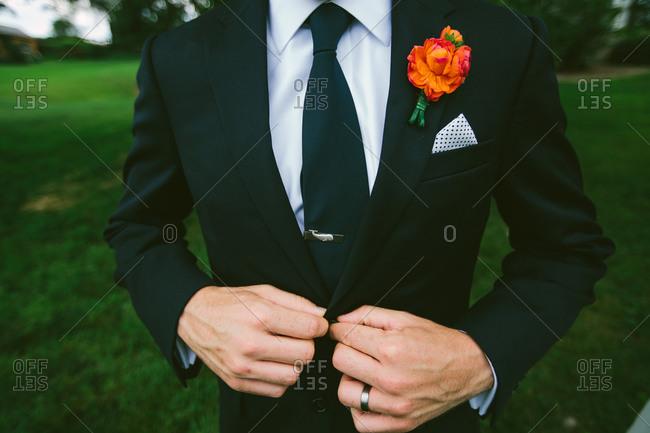 Man at wedding buttoning up tux jacket