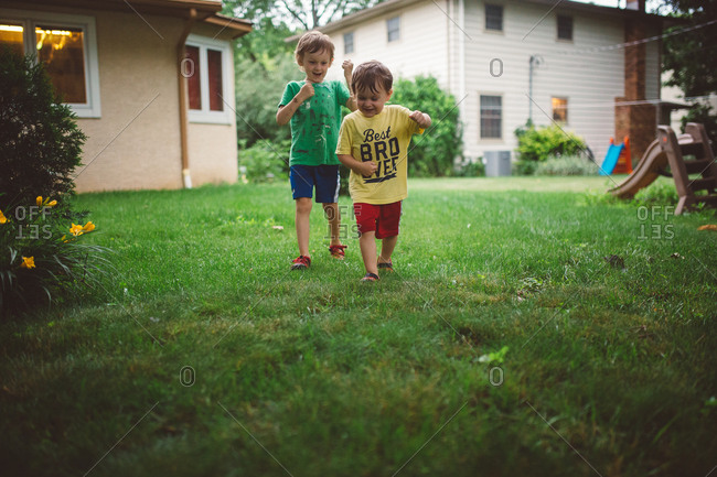 Two young boys running in back yard together at dusk