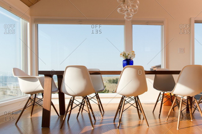 Modern dining table surrounded by windows in an oceanfront beach house