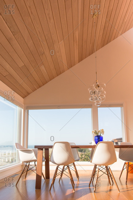 Modern dining table below a sloping ceiling in a modern beach house
