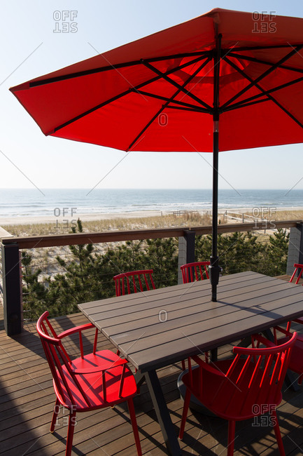 Outdoor dining table with red umbrella and chairs on an oceanfront deck