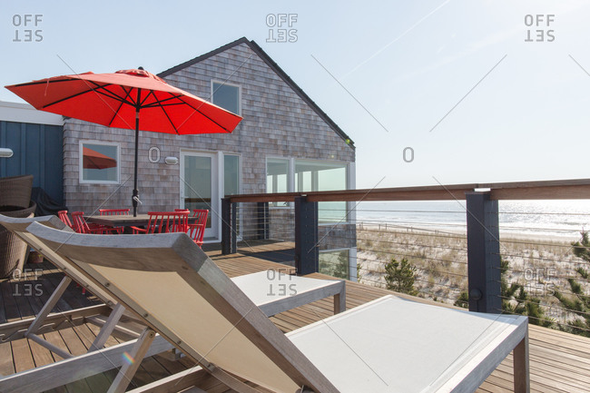 Chaise lounges and an outdoor dining table in an oceanfront beach house