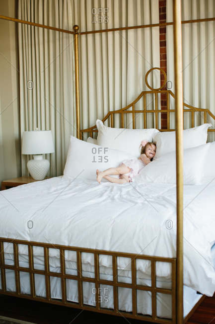 Toddler girl rolling in plush white bedding of a brass bed