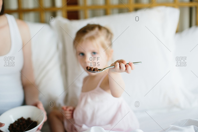 Toddler girl's outstretched arm holding a spoon offering chocolate cereal