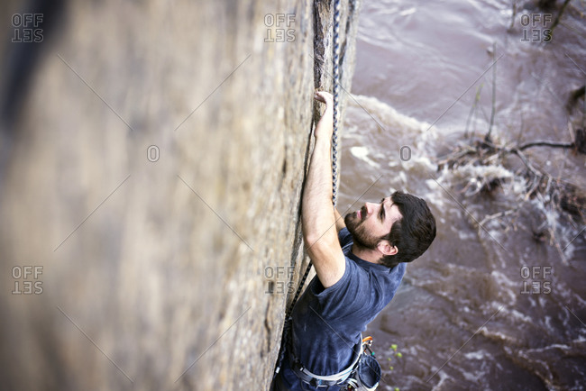 Man looks up while rock climbing