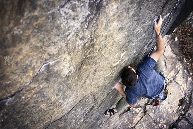Man climbing rock face - Offset