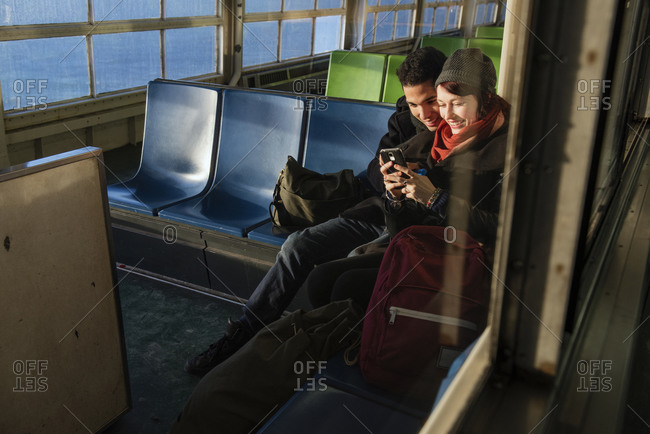 A couple cuddles together and looks at a cell phone on a ferry