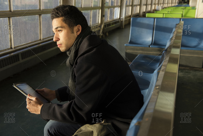 A young man sits on a ferry with his tablet