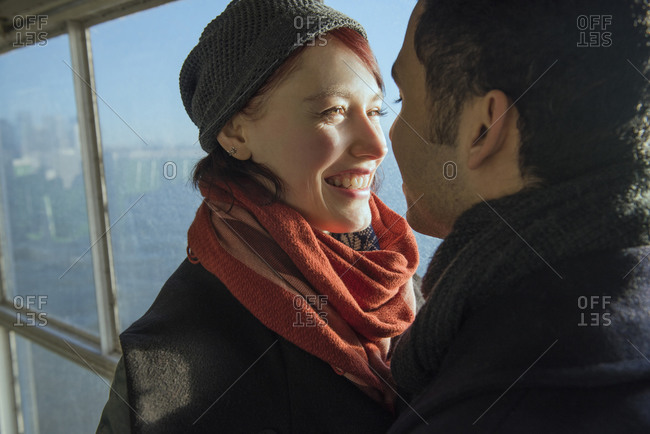 A woman smiles at her boyfriend while riding on a ferry
