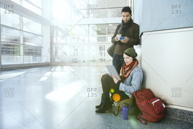 A traveling couple sits in a building lobby