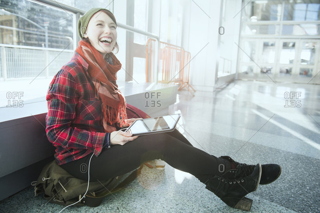 A woman laughs while using a tablet while waiting in a building lobby