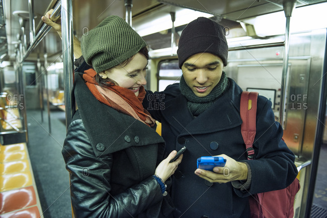 A couple looking at a cell phone together on the subway