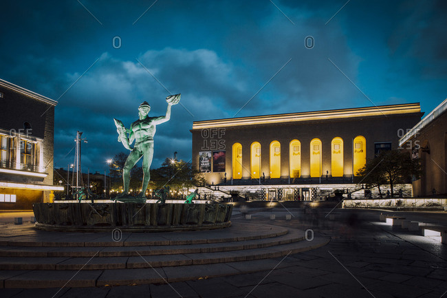 Gothenburg, Sweden - June 6, 2012: Poseidon fountain in front of illuminated concert hall against sky at night