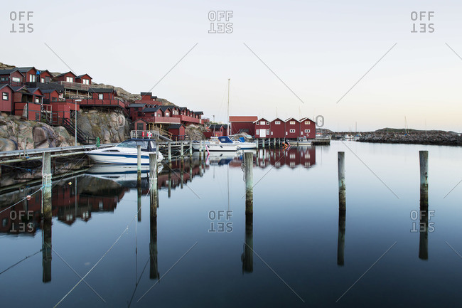 Boats moored on calm lake by houses against clear sky