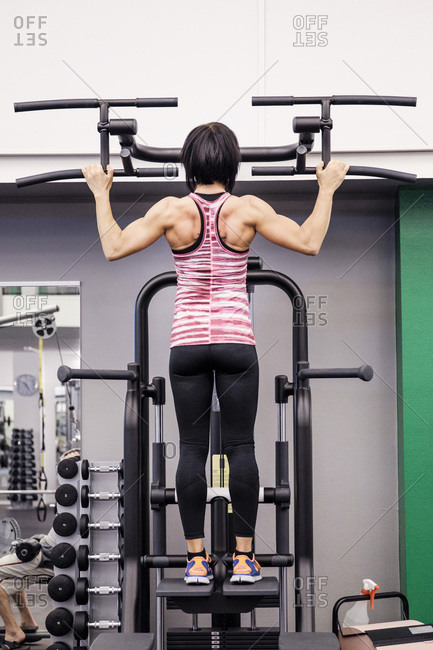 Rear view of sporty woman exercising at health club