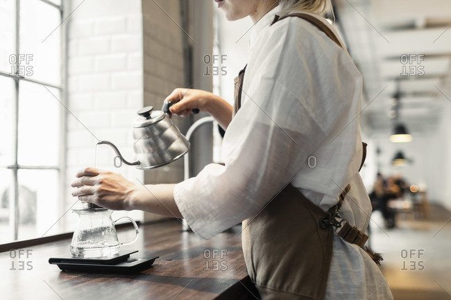 Female barista pouring boiling water in coffee filter at cafe counter