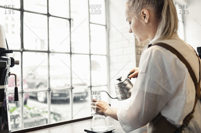 Side view of female barista preparing coffee at cafe counter by window