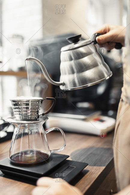 Barista pouring boiling water in coffee filter