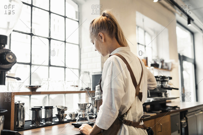Rear view of barista preparing coffee at counter
