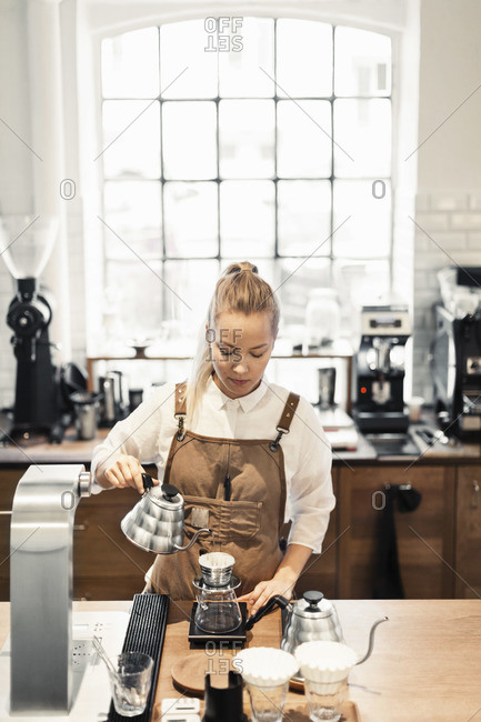 Female barista preparing coffee at cafe counter