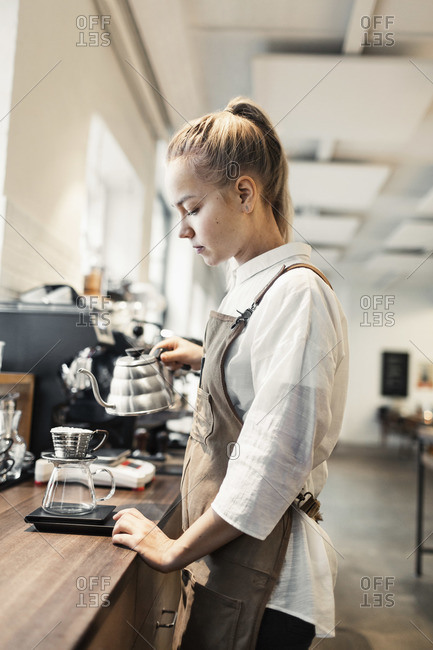 Side view of young female barista making coffee at counter