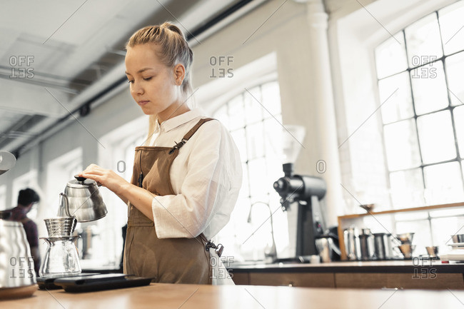 Female barista pouring boiling water in coffee filter at cafe
