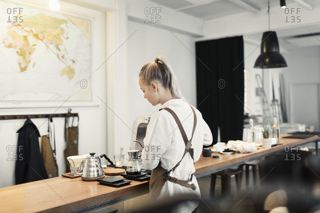 Rear view of young female barista preparing coffee at counter