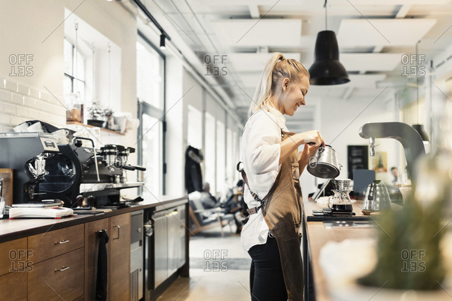 Side view of female barista preparing coffee at counter
