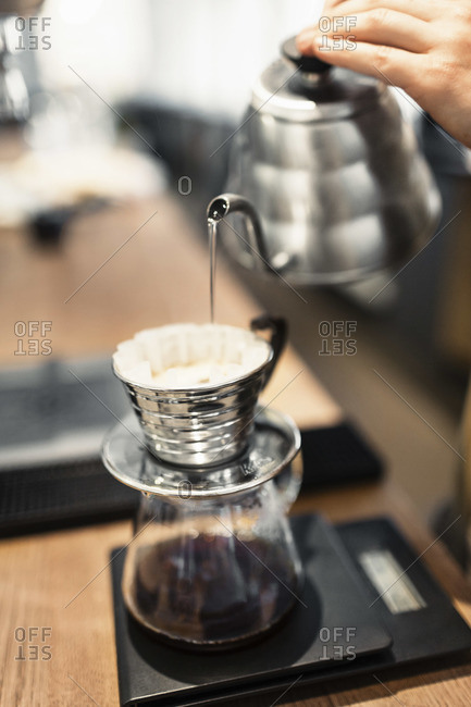 Barista pouring boiling water in coffee filter at counter