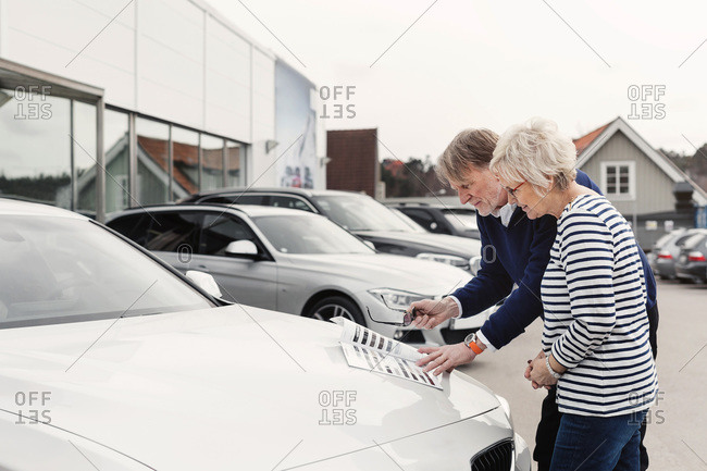 Senior couple reviewing brochure on car outside showroom