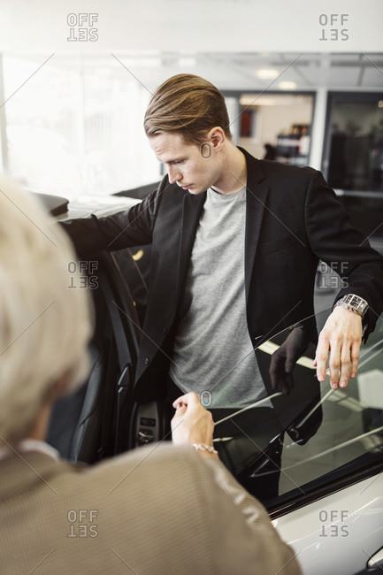Man examining car with saleswoman in foreground at shop