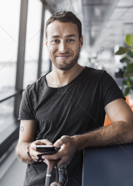 Portrait of smiling businessman holding mobile phone while leaning on cubicle in office