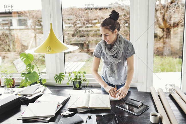 Female architect working at table in home office